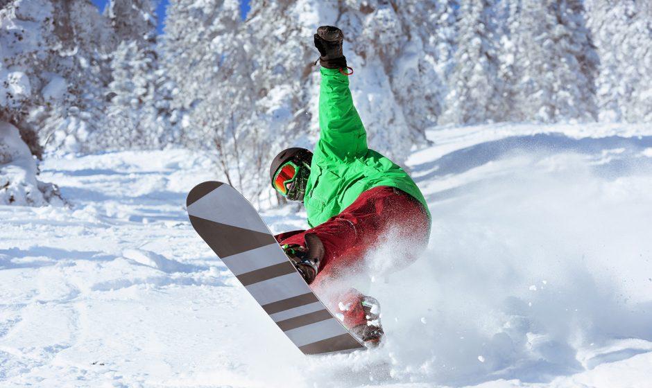 Snowboarder jumps in forest freeride in powder. Sheregesh ski resort