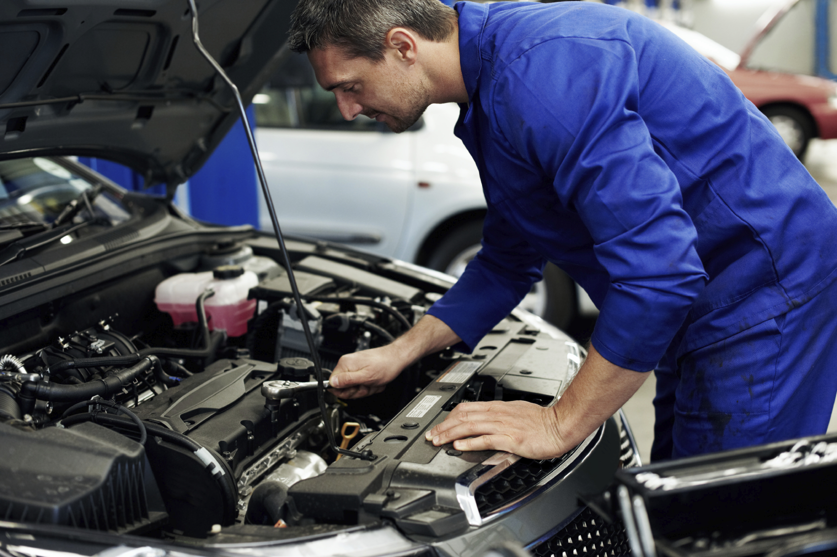 Accomplished mechanic tightening a sparkplug into place during a service at his workshop