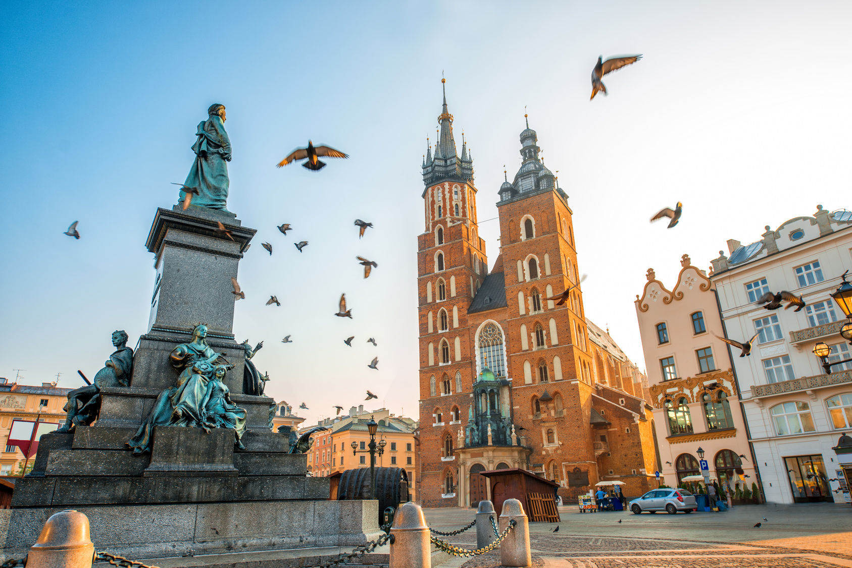 Old city center view with Adam Mickiewicz monument, St. Mary's Basilica and birds flying in Krakow on the morning