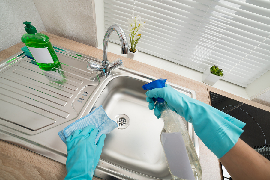 Person Hands In Blue Glove Cleaning Silver Kitchen Sink