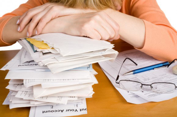 woman-leaning-on-stack-of-bills-e1283441586758