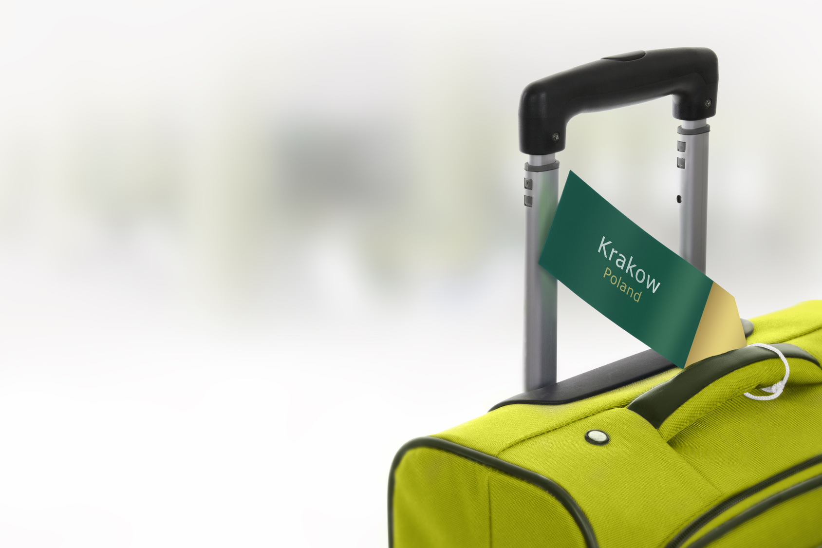 Krakow, Poland. Green suitcase with label at airport.