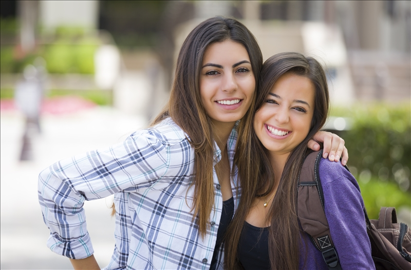 Portrait of Two Attractive Mixed Race Female Students Carrying Backpack on School Campus.