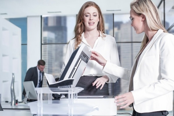 Businesswomen chatting by photocopier in office, colleagues using computer in background