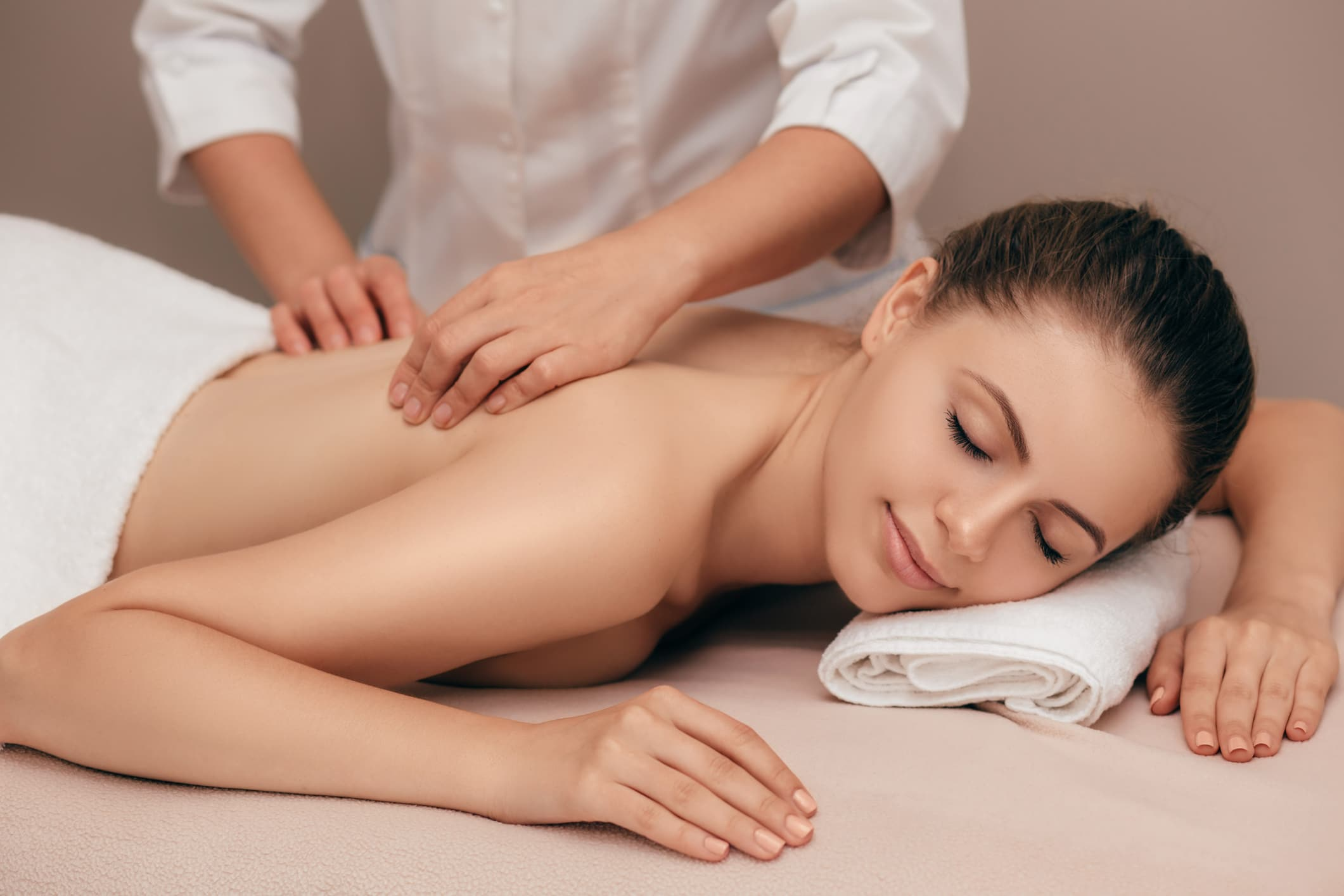 Young smiling woman receiving back massage from a massage professional at beauty salon