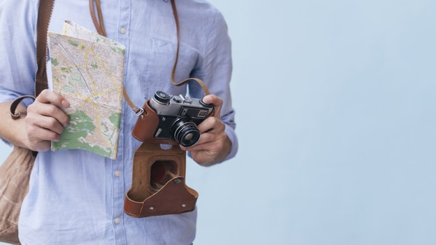 midsection-male-traveler-photographer-holding-camera-map-standing-against-blue-background_23-2148203069