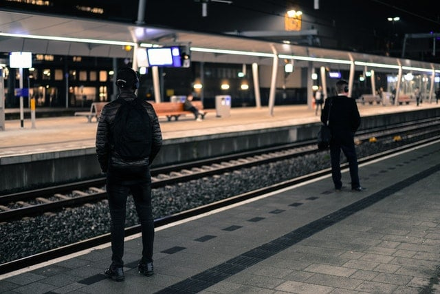 photo-of-two-men-standing-near-railway-station-722707