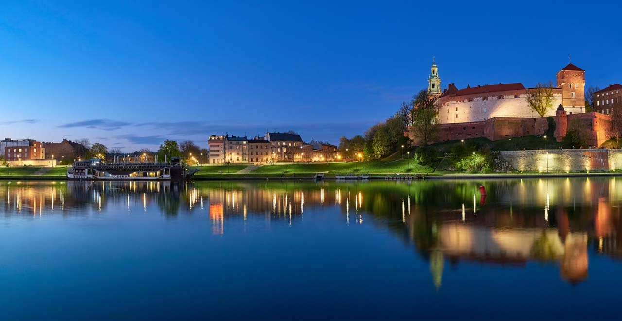Poland, Krakow, Wawel hill at night, panoramic view from the other bank of river Vistula