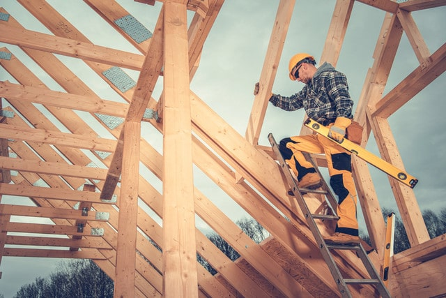 Caucasian-Wood-Skeleton-Frame-Worker-on-Top-of-New-Constructed-House-Structure-Staying-on-Ladder-wit